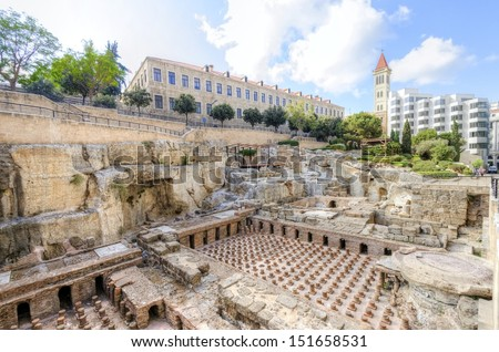A view of the archaeological ruins of the ancient roman baths discovered in downtown Beirut, in Lebanon, surrounded by modern buildings and Saint Louis Des Capucins cathedral in the bacground - stock photo