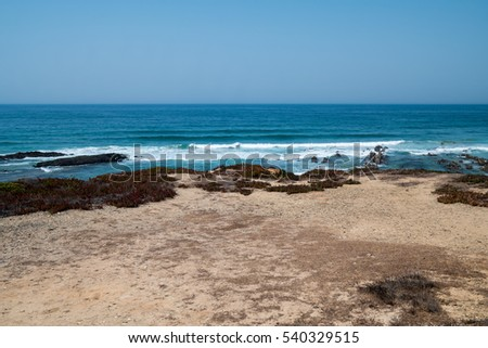 A view of the atlantic ocean from a beach showing cliffs and rocks