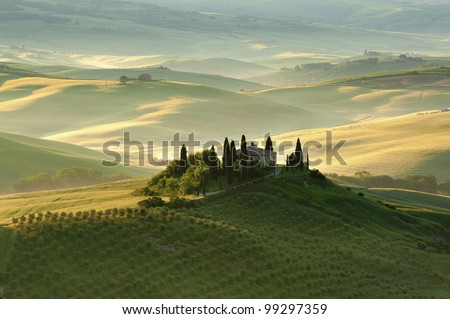 A view of The Belvedere, Val d'Orcia, Tuscany, at 4:30 am, as the first rays of the sun begin to light the landscape.