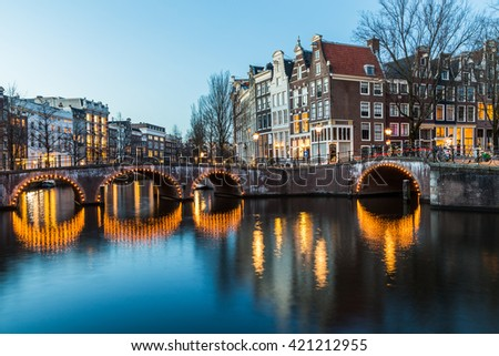 A view of the bridges at the Leidsegracht and Keizersgracht canals intersection in Amsterdam at dusk.