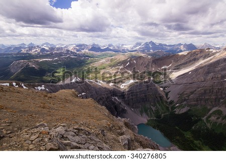A view of the Canadian rockies. Lakes, peaks, meadows, snow and white clouds. - stock photo
