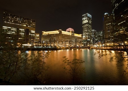 A view of the Chicago river and the Merchandise Mart with other commercial buildings at night. - stock photo