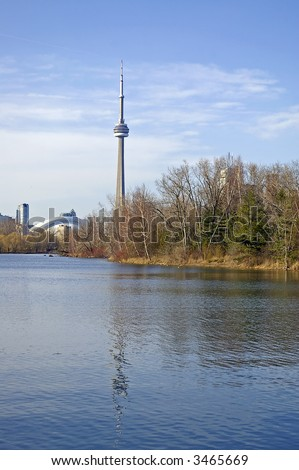 A view of the CN Tower from Centre Inland.  Skyline view is reflected in the water, and budding trees visible along right shoreline.