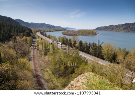 A view of the Columbia River Gorge from the Oregon side showing the waterway, the highway, and the railway as modes of transportation.