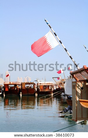 A view of the dhow harbour in Doha, Qatar, with the focus on Qatar's national flag. - stock photo