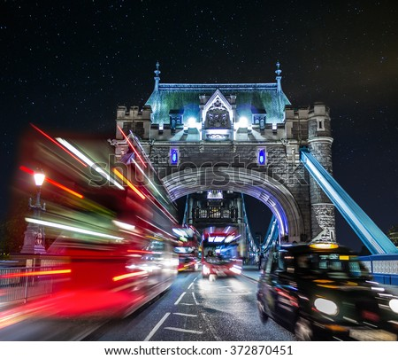 A view of the entrance to Tower Bridge with typical London traffic and starts in the sky - stock photo