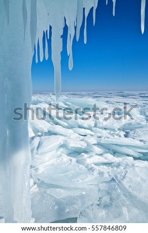 A view of the frozen lake Baikal from the ice grotto with icicles. Winter natural background