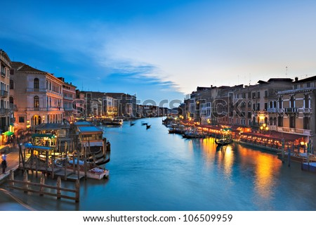 A view of the Grand Canal from the Rialto Bridge in Venice, italy shows bustling tourists as dusk replaces daylight. - stock photo
