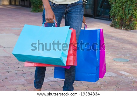 A view of the lower half of a person walking on a sidewalk in the city carrying colorful shopping bags. - stock photo