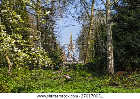 A view of the magnificent Albert Memorial through the trees of Kensington Gardens, London. - stock photo
