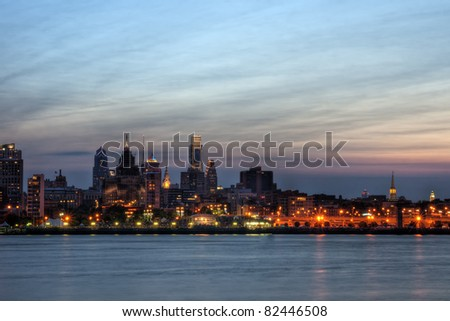 A view of the Philadelphia skyline at twilight with buildings illuminated. - stock photo