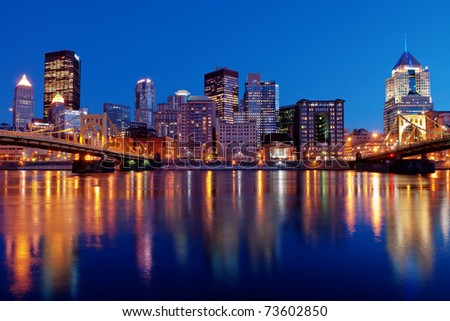 A view of the Pittsburgh, Pennsylvania cityscape at night overlooking the Allegheny River with views of the Roberto Clemente Bridge and Andy Warhol Bridge. - stock photo