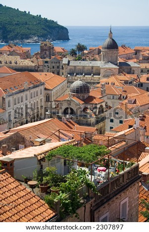 A view of the roofs of Dubrovnik with an emphasis on a rooftop garden, the cathedral and the St-Blaise church - stock photo