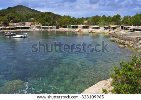 a view of the Sa Caleta cove in Ibiza Island, Spain, with its traditional fishermen shelters - stock photo