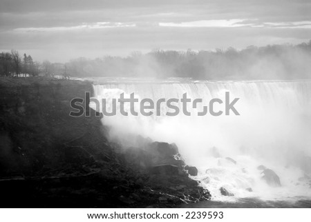 A view of the smaller falls at Niagara covered in rising mists (black and white). - stock photo