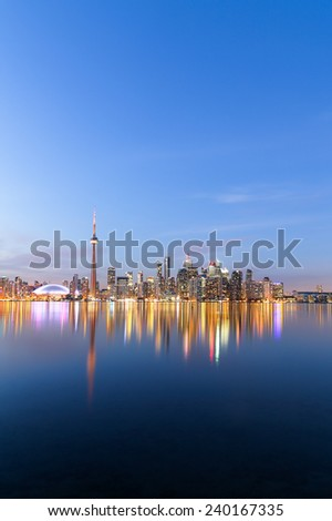 A view of the Toronto Skyline at twilight in the winter showing buildings and reflections in the water - stock photo