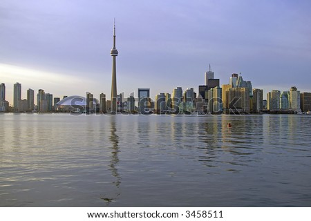 A view of the Toronto skyline including the CN Tower, Rogers Centre (formerly Skydome), and the Financial District, taken from Lake Ontario near sunset. - stock photo