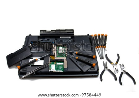 A view of the underside of an open computer surrounded by precision tools isolated on white - stock photo