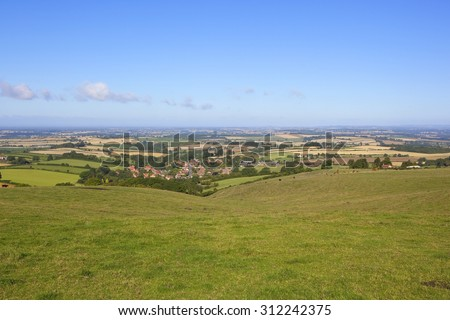 a view of the vale of york from a hillside meadow on the yorkshire wolds england under a blue sky in summer - stock photo