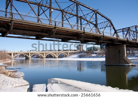 A view of the Victoria Bridge and Broadway Bridge in Saskatoon, Canada on a sunny day in winter. - stock photo