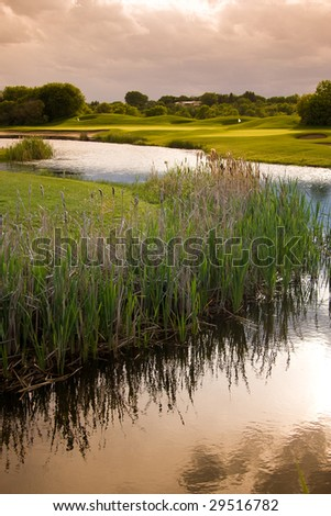 A view of the water and marsh near a golf course.  The dramatic sky and reflections give a peaceful feeling. - stock photo