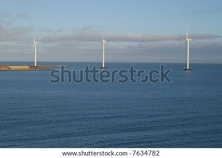 A view of three tall wind-powered electricity generators built just offshore in Frederikshavn, Denmark. - stock photo