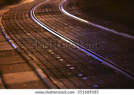 A view of tram rails in city at night.