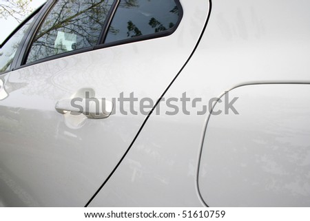 A view of white car rear door and window.