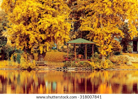 A view on an autumn park with lake and an arbor. Lietzensee, Berlin, Germany.