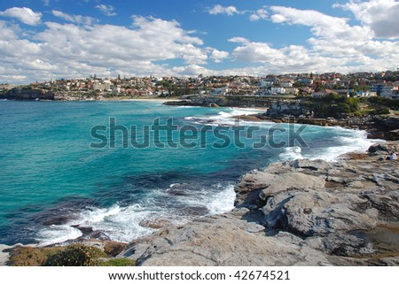 A view on Bronte Bay with beuatiful azure ocean and blue sky with clouds - stock photo