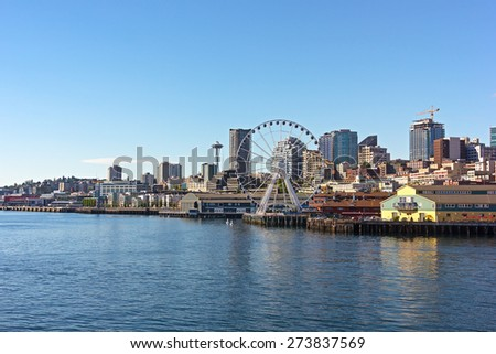 A view on Seattle downtown from the waters of Puget Sound. Piers, skyscrapers and Ferris wheel in Seattle city before sunset. - stock photo