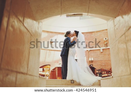A view on the kissing couple standing in the corridor's tunnel - stock photo