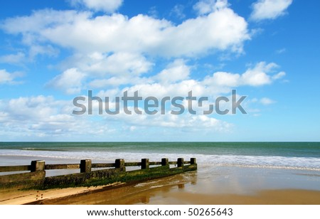 A view out to sea from a sandy beach swept clean and smooth by the tide, with a beautiful deep blue sky above - stock photo