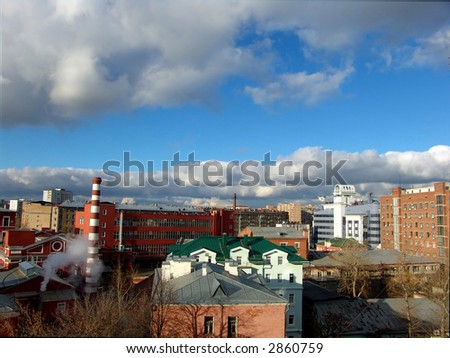 A view over city roofs with industrial and office buildings and a nice cloudy sky