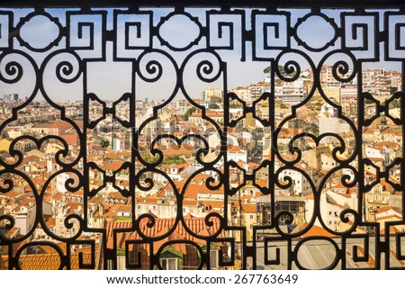 a view over Lisbon, Portugal's capital, through the frame of a traditional balcony in the St. George castle's hill - stock photo