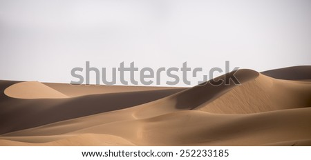 A view over some smooth brown sand dunes in the Sahara desert in Erg Chegaga in Morocco in Morocco in the spring during a hot sunny day. - stock photo