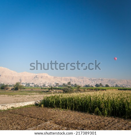 A view over the Nile floodplain near Luxor, Egypt, with a hot air balloon flying over the Valley of the Kings in the distance. - stock photo
