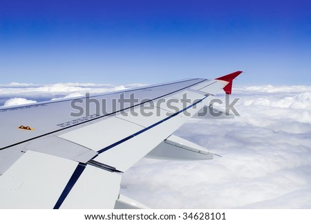 a view though an airplane window where one can see the wing and beautiful cloudy sky - stock photo