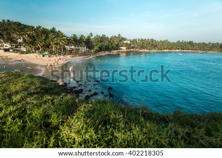 A view to the bay and beach with tropical trees from a hill