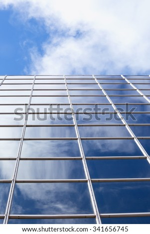 A view up the side of a glass corporate building with the sky and clouds refected in it. - stock photo