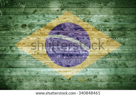 A vignetted background image of the flag of Brazil painted onto wooden boards of a wall or floor. - stock photo