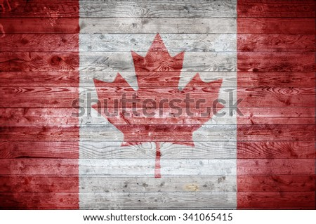 A vignetted background image of the flag of Canada painted onto wooden boards of a wall or floor. - stock photo