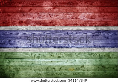 A vignetted background image of the flag of Gambia painted onto wooden boards of a wall or floor. - stock photo