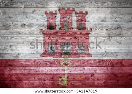 A vignetted background image of the flag of Gibraltar painted onto wooden boards of a wall or floor.