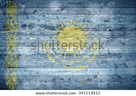 A vignetted background image of the flag of Kazakhstan painted onto wooden boards of a wall or floor. - stock photo