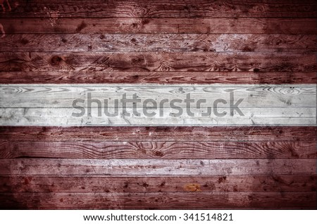 A vignetted background image of the flag of Latvia painted onto wooden boards of a wall or floor. - stock photo