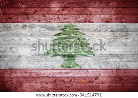 A vignetted background image of the flag of Lebanon painted onto wooden boards of a wall or floor. - stock photo