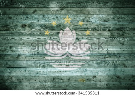 A vignetted background image of the flag of Macau painted onto wooden boards of a wall or floor. - stock photo