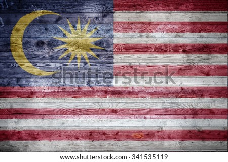 A vignetted background image of the flag of Malaysia painted onto wooden boards of a wall or floor. - stock photo