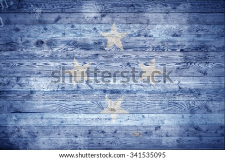 A vignetted background image of the flag of Micronesia painted onto wooden boards of a wall or floor. - stock photo